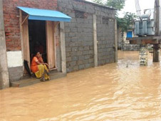 A woman sits desolately outside her flooded home