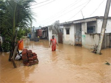 A woman wading through the flood waters