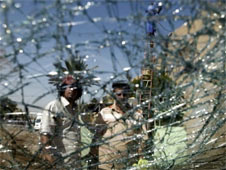 Iraqis are seen through a shattered windshield of a vehilce at the scene of a car bomb attack that killed dozens of people in Baghdad, Iraq on 30 September