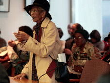 Detroit city resident stands up and leads a prayer during a public meeting of the Detroit City Council in Detroit, Nov. 20