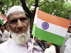 A Muslim man holding the Indian tricolour flag