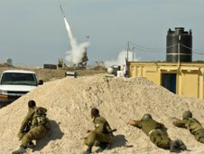 Israeli soldiers take cover as an Israeli missile is launched from the Iron Dome defence missile system, designed to intercept and destroy incoming short-range rockets and artillery shells, in the southern Israeli city of Ashdod in response to a rocket launched from the nearby Palestinian Gaza Strip on November 18, 2012