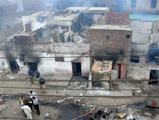 Pakistani police officials examine the burnt out houses of members of the Christian community attacked by Muslim demonstrators